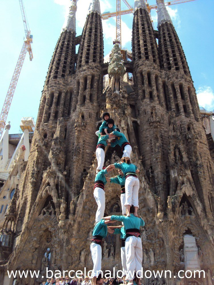 A group of castellers form a human tower in front of the Sagrada Familia Basilica, Barcelona