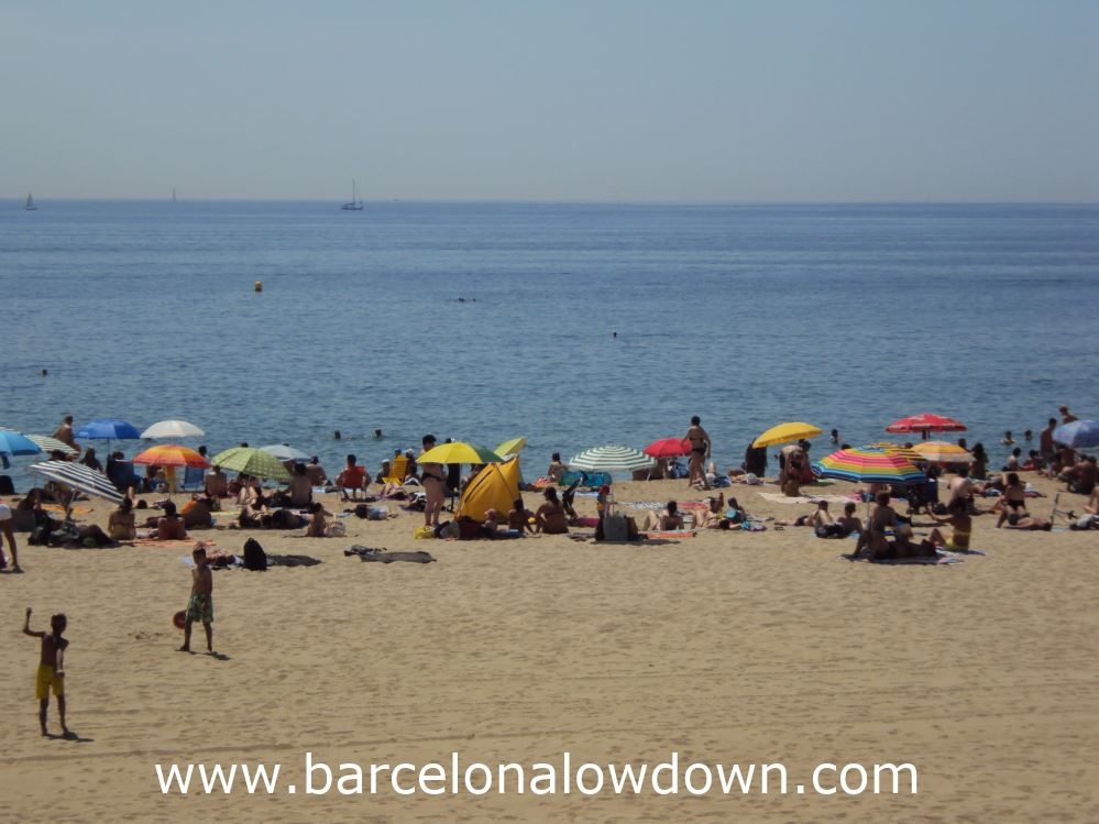 People enjoying the sunshine on Barcelona's beach, playing beach tenis, swimming or shading under parasols