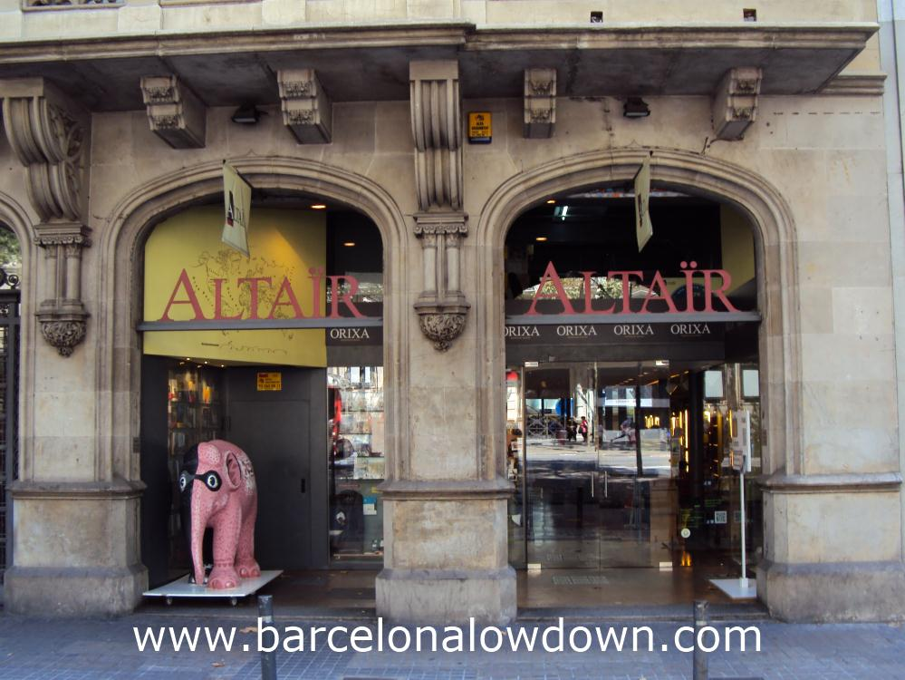 Photo of the Altaïr travellers bookshop barcelona on Gran Via with a masked pink elephant in the foreground