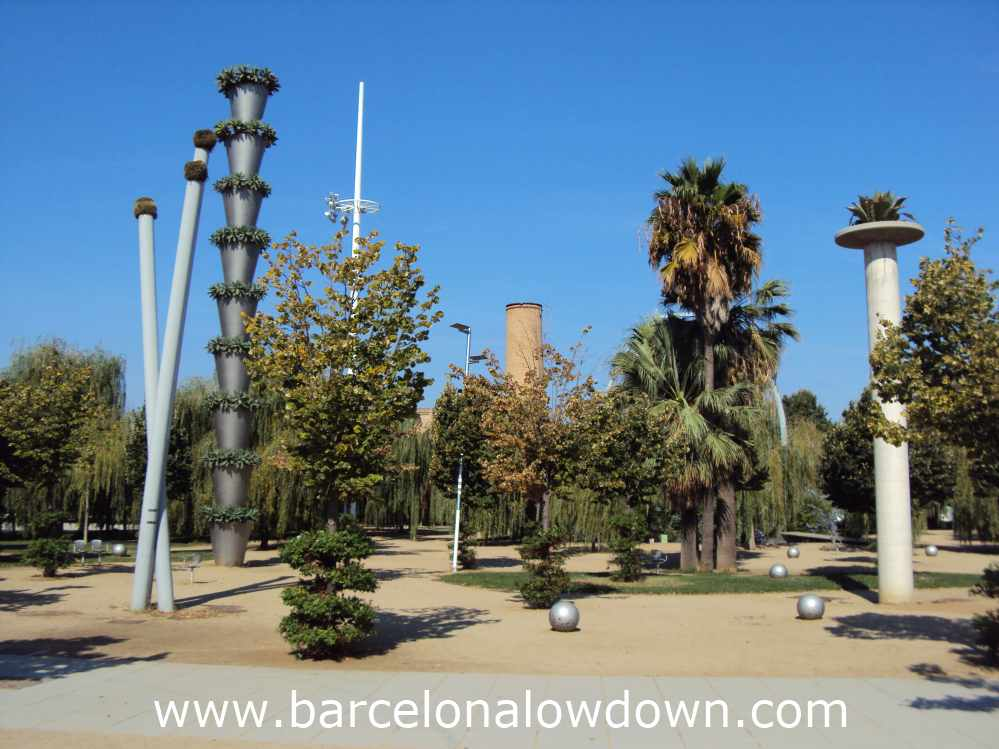 Willows, palm-trees and architecture in a park in Barcelona