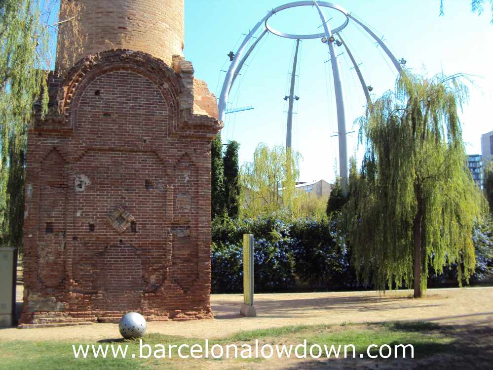 Old brick chimney in front of a steel dome in Poblenou's Central Park, Barcelona
