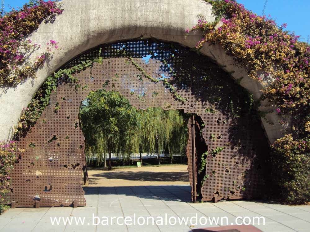 Iron gateway framed by purple flowers, Poblenou Barcelona