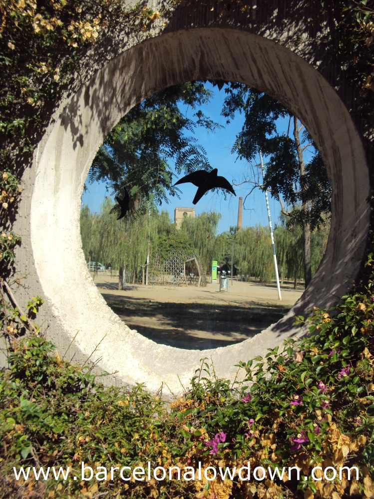 Photo of Poblenou's Central Park taken through one of the portholes in the perimeter wall