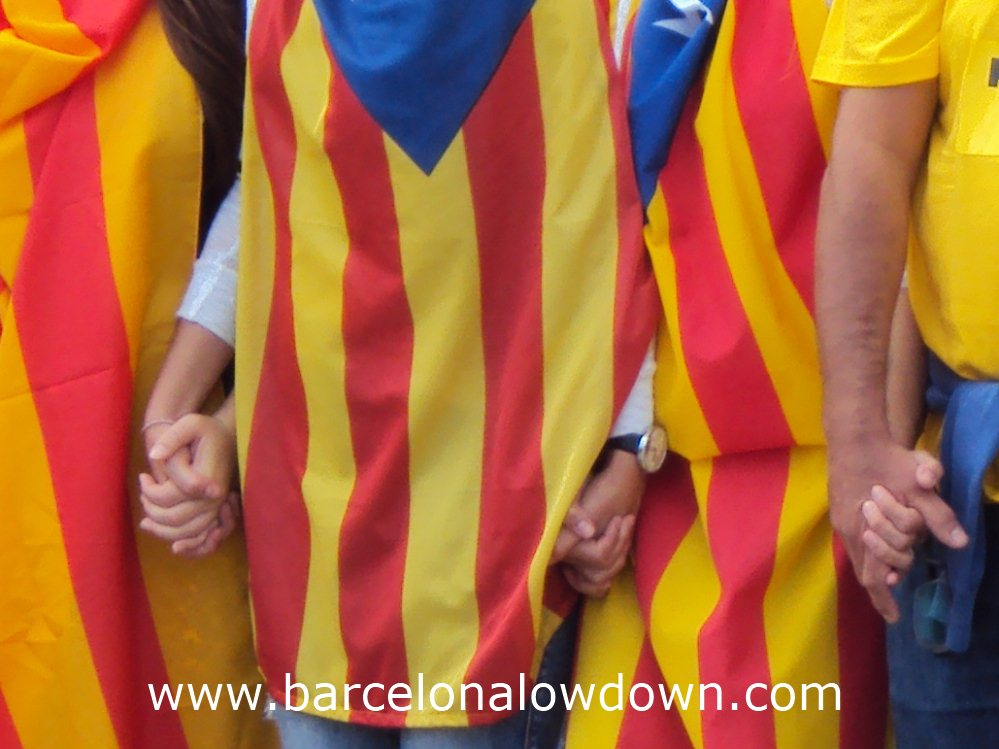 """Catalans dressed in Catalan independence flags holding hand as part of the 400km long """"Catalan Way"""" in Barcelona"""