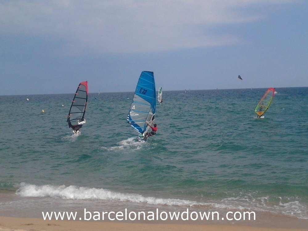3 windsurfers and a kiesurfer sailing at Badalona beach near Barcelona