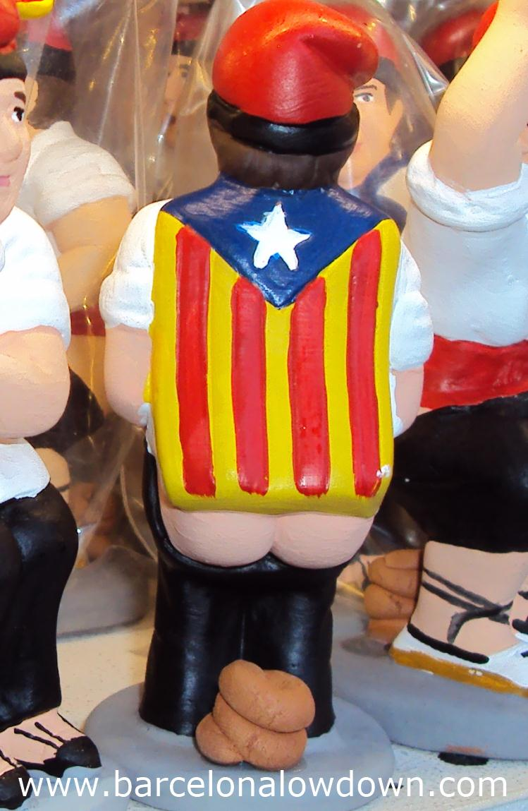 Caganer figurine draped with a Catalan nationalist flag or estelada