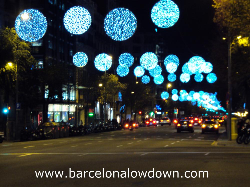 Christmas lights hanging above cars and taxis in central Barcelona