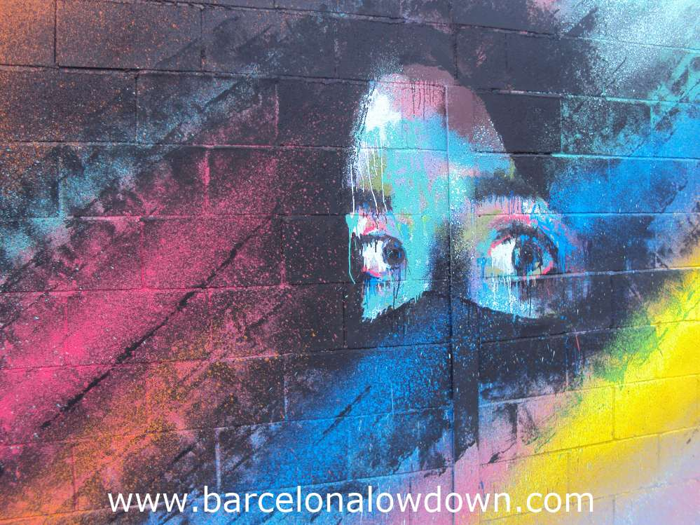 Painting of a girls eyes on a multicoloured black background, painted on a breezeblock wall.