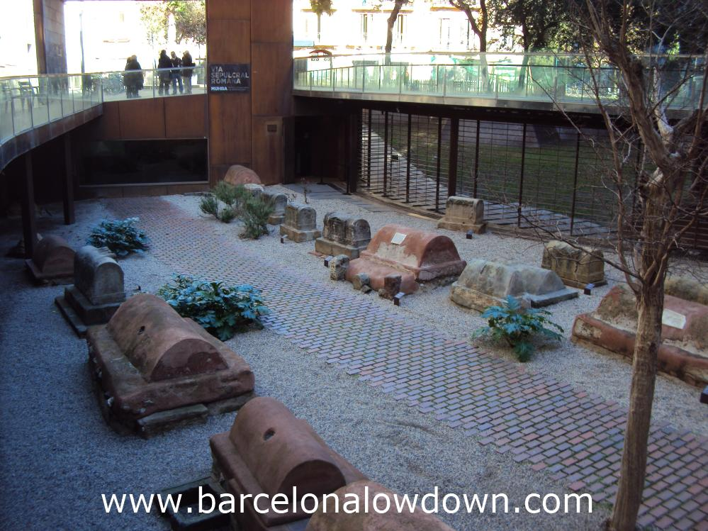 A group of tourists looking down on the ancient Roman graveyard at the MUHBA Via Sepulcral Romana Barcelona