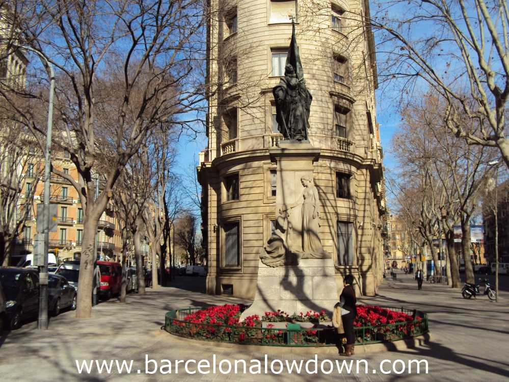 Statue of Rafael Casanova in the Eixample district of Barceona, The statue is surrounded by trees and elegant old buildings.