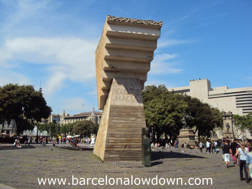 A group of tourists filing past the Francesc Masià monument in Catalonia Square Barcelona