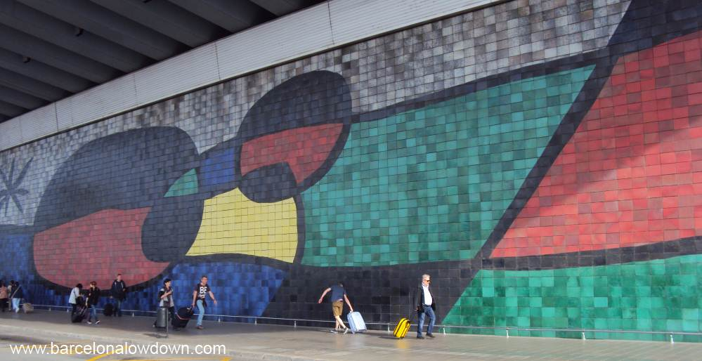 Tourists with suitcases walking in front of a giant tiled mural by Catalan artist Joan Miro