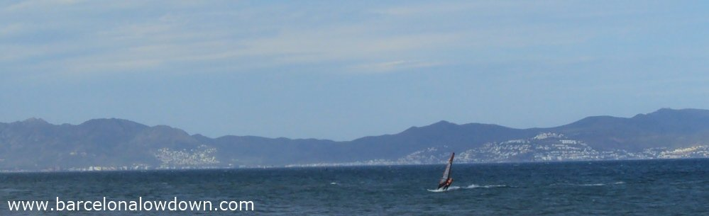 A windsurfer sailing in the Bay of Roses on the Spanish Costa Brava