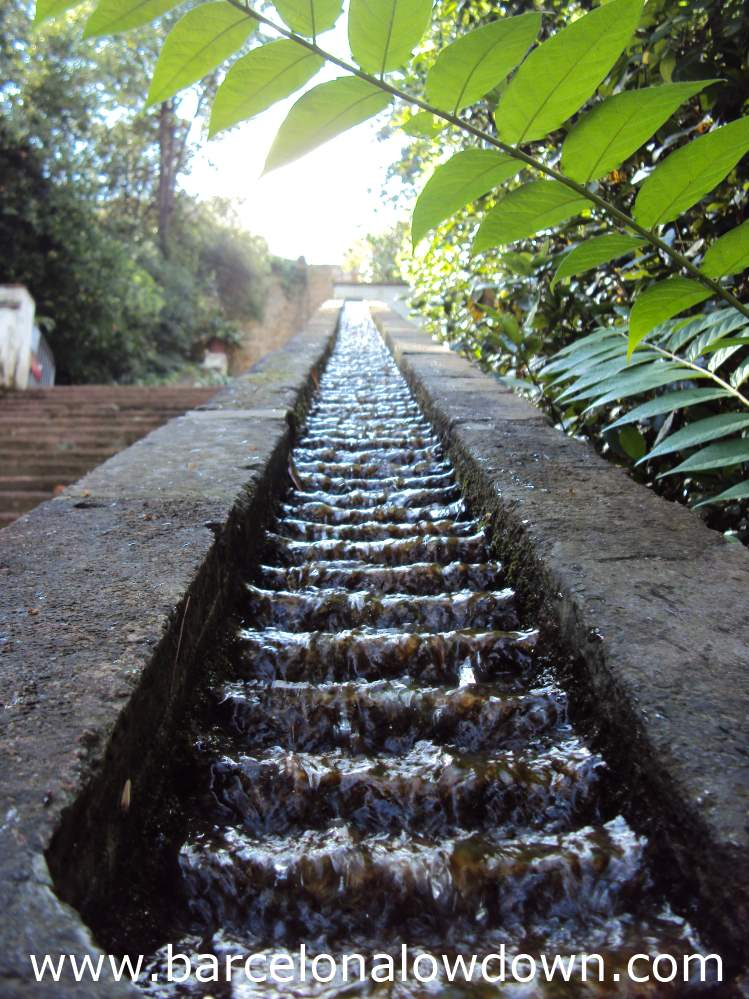 Mini waterfalls cascade down the handrail of the Generalife steps