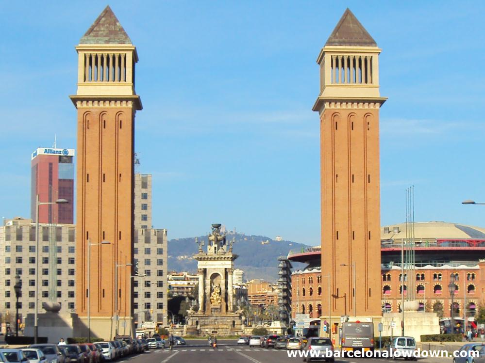 Photo of Plaza d'Espanya square with the venetian towers in the foreground and the fountain and Les Arenys shopping centre behind.