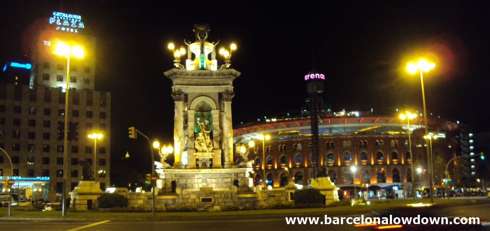 Plaça d'Espanya Barcelona at night. The neoclasical fountain floodlit with the arenys shopping centre and Catalonia Plaza hotel in the background.