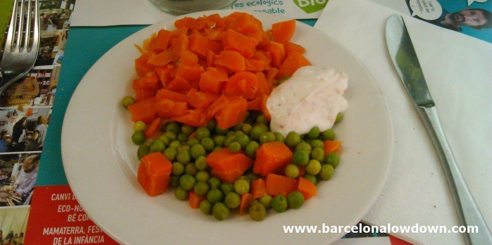 Simple dish of fresh carrots and pease served with delicious yougurt sauce at Arc Iris vegetarian restaurant Barcelona