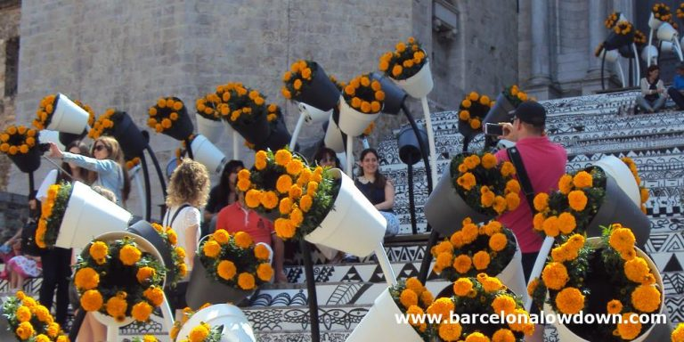 Tourists taking photos amongst the flowers at Geronas famous flower festival in Northern Spain