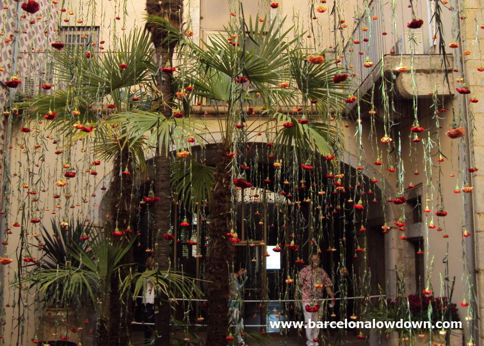Hundreds of hanging flowers which decorate a patio inside an old building in the historic Jewish quarter of Girona, Catalonia