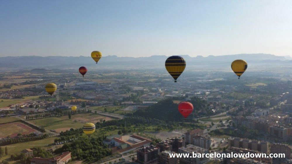 8 colorful hot air balloons slowly rising over the city of Vic near Barcelona with distant views of the Catalan mountains too the north.
