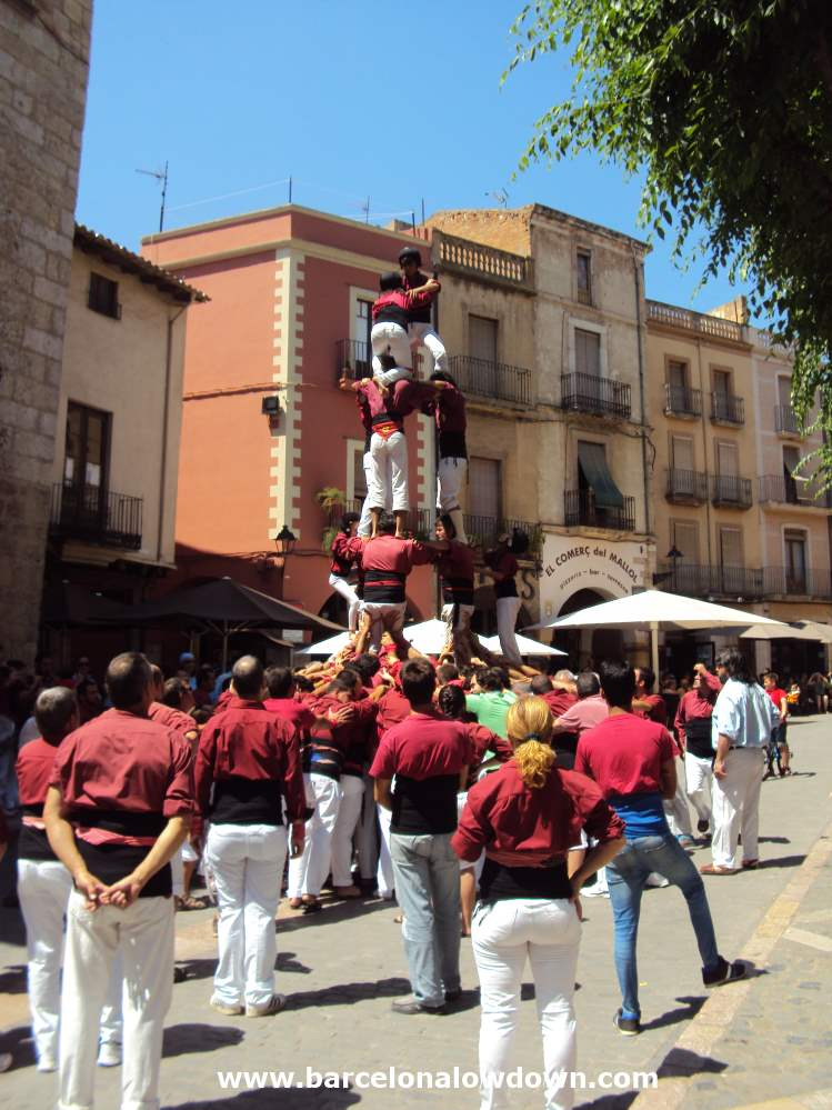 A Coll or group of castellers performimg a human tower in the medieval Catalan village of Montblanc near Tarragona