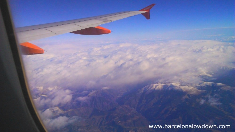 View of snow capped mountains out of the window of an easyjet flight between London Gatwick and Barcelona airport.