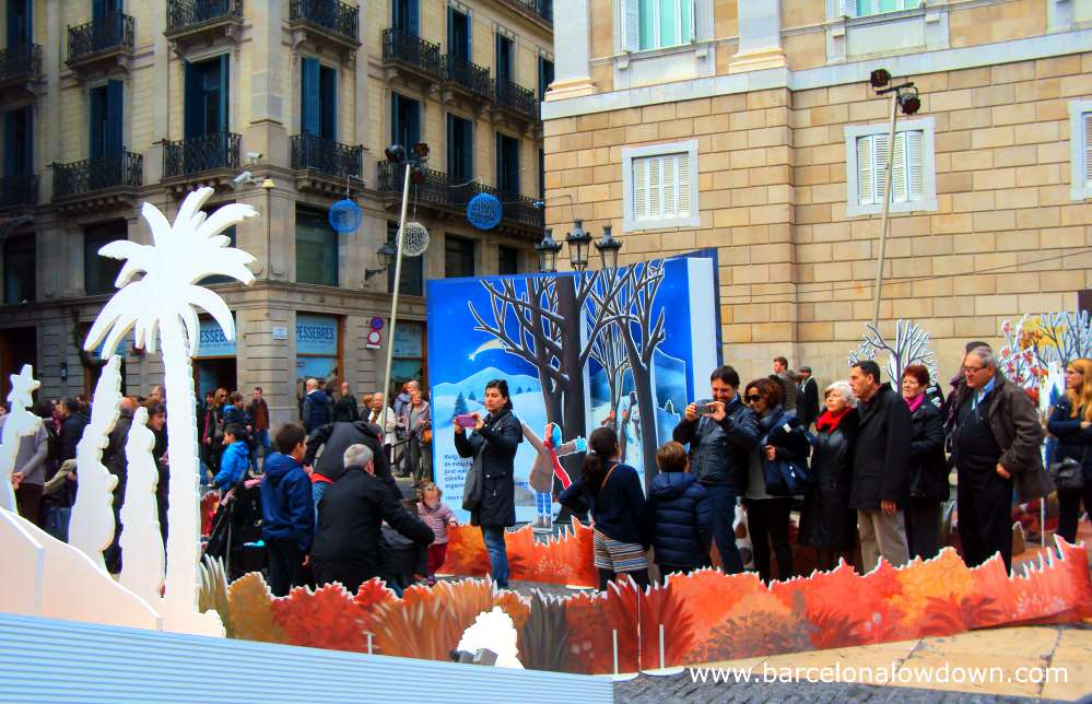 Families queuing up to take photos with the nativity scene in front of Barcelona city hall