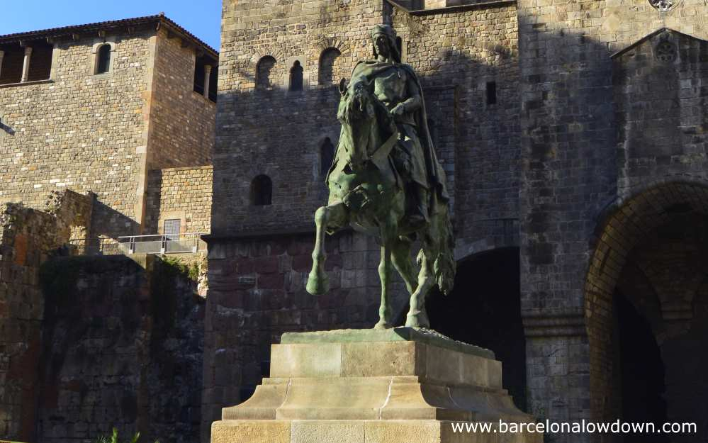 Equestrian statue of Ramon Berenguer III in front of a stretch of Barcelona's ancient Roman walls.