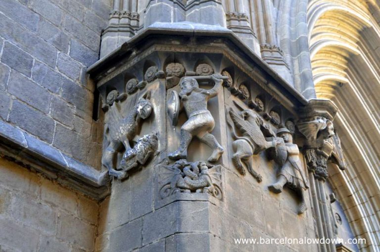 Stone carving of Wilfred the Hairy slaying a dragon with a wooden staff nect to the door of Barcelona cathedral