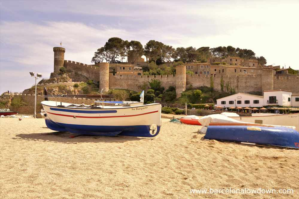 Traditional fishing boats on the beach in front of the medieval castle, Tossa de Mar