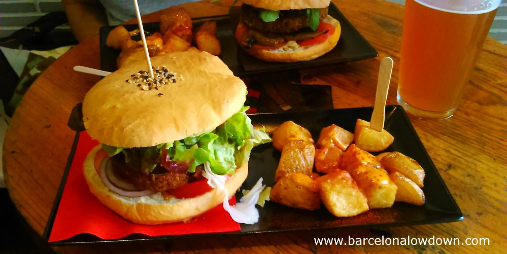 Vegan burgers in hand baked bread rolls asrved with fried potatoes and craft beer in Cat Bar Barcelona