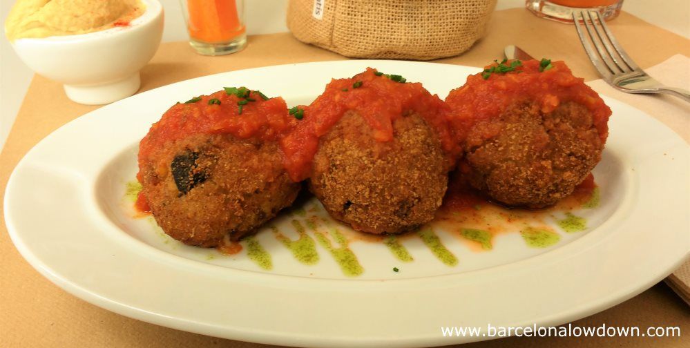 Starter of 3 arancini made with locally sourced rice and cheese served at the Aguaribay vegetarian restaurant in Barcelona