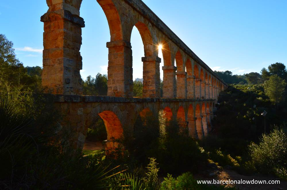 Photo of the Roman aqueduct near Tarragona, Spain. The photo was taken early in the morning and the sun shines between the arches of the aqueduct.