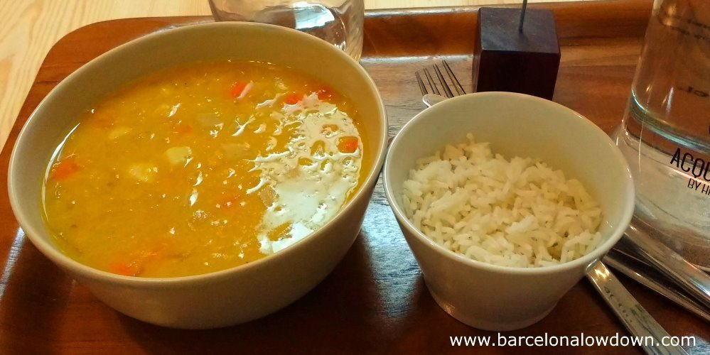 A bowl of delicious vegetarian soup served with rice and drinking water at the the Sopa soup restaurant in Barcelona's Eixample district.