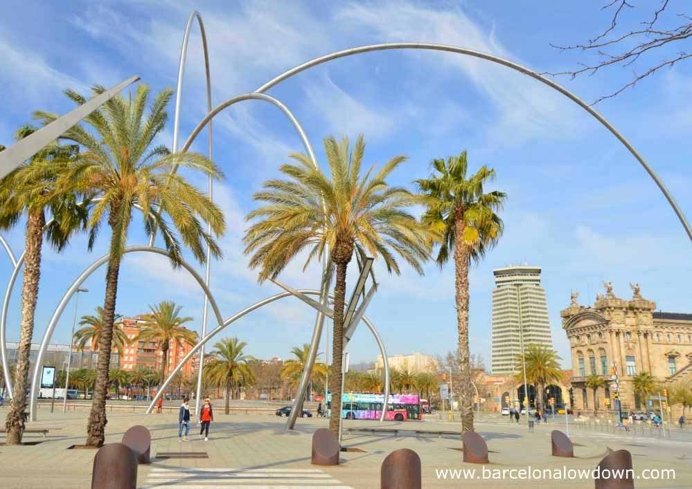 Photo of Andreu Alfaro's waves statue taken on a sunny day in February in Barcelona. You can see the Barcelona custom house, the Maritime Museum and an open top tour bus in the background.