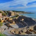 The ancient Roman amphitheatre of Tarragona with views of the beach and blue Mediterranean sea in the background