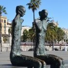 A bronze statue of a couple by Barcelona's old port. The sculpture was made in 1998 by Chilean artist LautaroDiaz