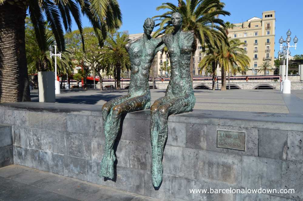 Bronze statue of a loving couple located near Barcelona's historic port and seafront area