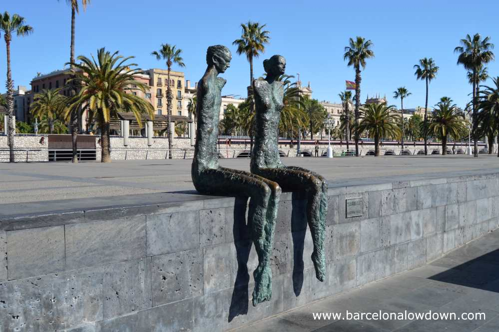 The couple statue by Lauturo Díaz sit alone on a wall in front of old buildings beside Barcelona's historic old port the Port Vell
