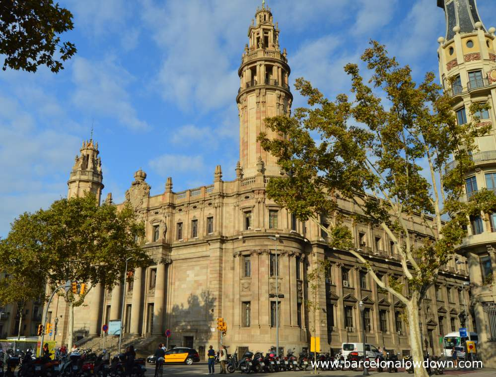 The exterior of Barcelona central post office seen from the other side of Via Laitana. There are two trees in the foreground and a line of parked motorbikes on the kerb.