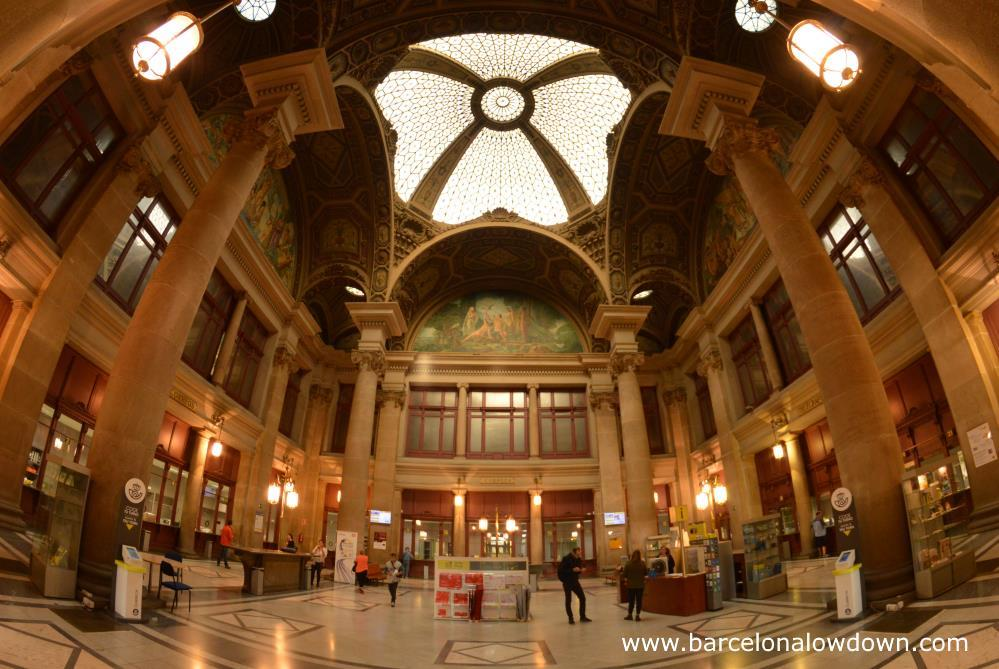 Interior view of Barcelona Post Office thru a fisheye lense. You can see the glase ceiling dome and mosaics which decorate the ceiling and upper wals. Also the slender corinthian columns whic support the roof and old fashioned interior. The photo shows the typical distortin associated with fisheye lenses.