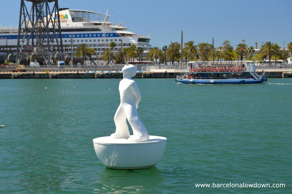 One of the two white figures which make up the mirsestels or stargazer monument in the old harbour, Barcelona. In the background you can see a cruise ship and one of the small boats which do harbour tours.