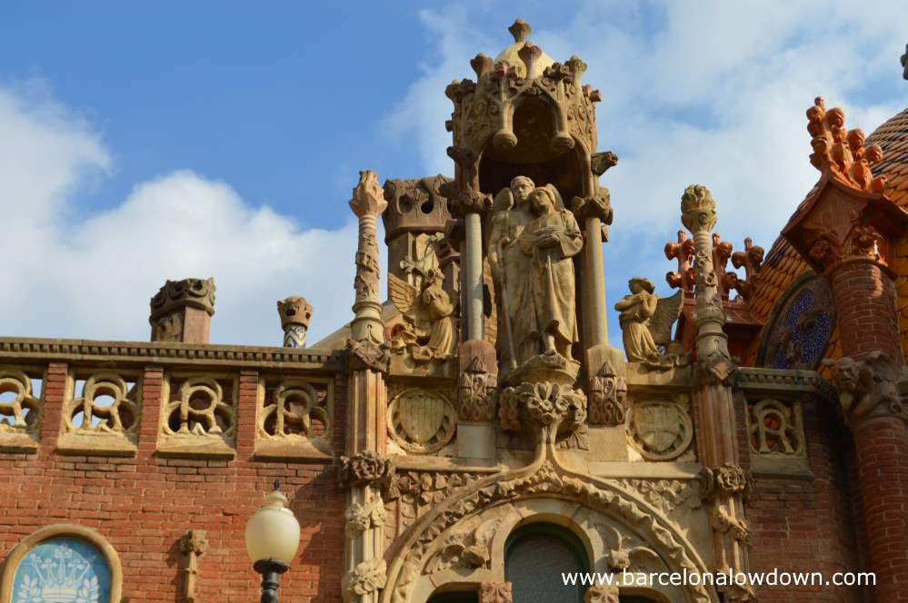 Photo of statues and other decorative features above one of the entrances to the old Hospital de Sant Pau Art Nouveau site in Barcelona.