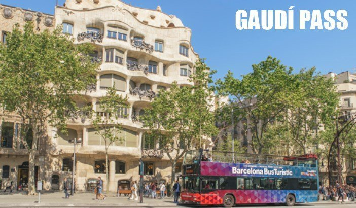 An open topped city tour bus parked in front of the La Perdrera building on Passeig de Gracia Barcelona