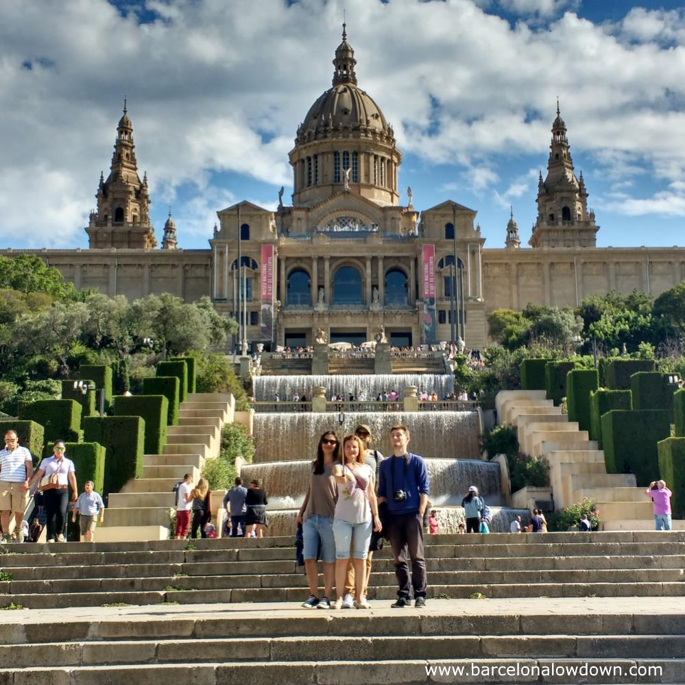 A group of people taking a selfie in front of the Palau Nacional in Barcelona. They probably uploaded it to Instagram and Facebook to show their friends back home what a good time they were having.