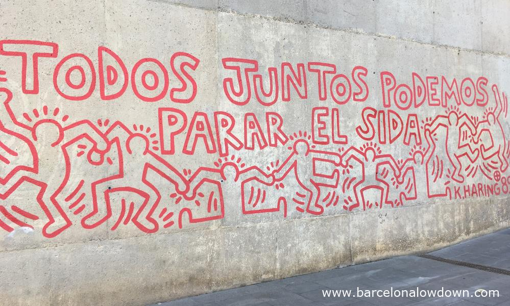 Todos juntos podemos parar el SIDA (Together we can stop aids) written in blood red letters in a mural by Keith Haring in Barcelona