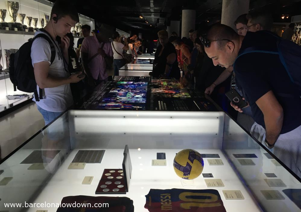 Barça fans looking at the memorabilia (Including one of Messi's shirts) on display in the FC Barcelona museum during the Camp Nou tour.