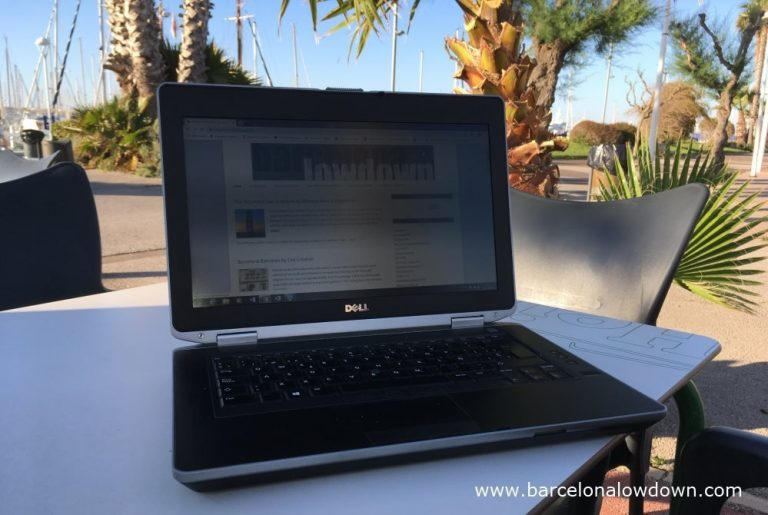 Photo of a laptop on a table in a sunny Marina near Barcelona - the barcelona lowdown blog is on the screen