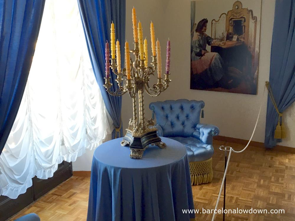 Ornate surrealist candlesticks ontop of a table covered bt a blue tebleclosth in Gala Dali castle in Pubol Spain