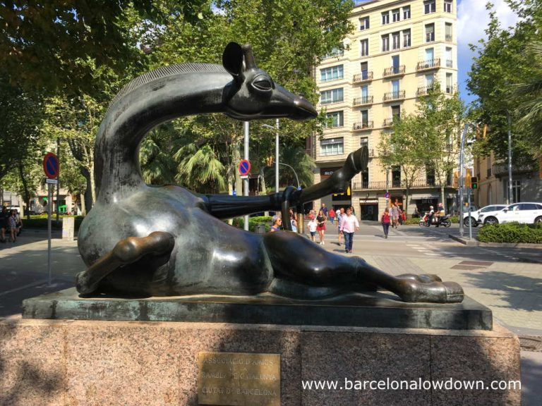 Bronxe statue of a Giraffe by Josep Granyer, the giraffe is reclining in a sexy pose, it's tail draped over one hoof